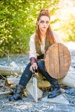 Female Viking Character. A beautiful female shield maiden viking character with fur and saex knife in the foothills of a mountain. Fashion editorial influences stock images
