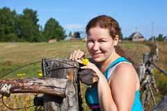 Female villager standing in front of wooden fence. Woman villager standing in front of wooden fence Stock Photography
