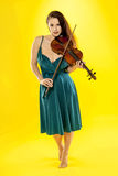 Female violinist. A beautiful female violinist over a yellow background Royalty Free Stock Image