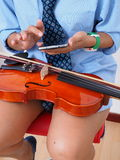 Female violinist pauses to use  mobile phone. Female violinist her violin on her lap pauses to use smartphone Royalty Free Stock Image