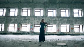 Female violinist is playing the instrument in a rundown hall. 4K stock footage