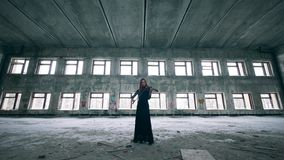Female violinist is playing the instrument in an unkempt building stock video