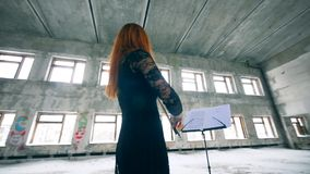 Female violinist is playing while looking at the music rack. 4K stock footage