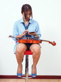 female violinist texting on mobile phone Royalty Free Stock Images