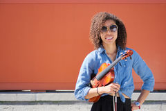 Female violinist with violin under arm smiling at camera Royalty Free Stock Image