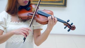 Female violinist in a white dress is playing the instrument. 4K stock footage