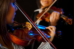 Female violinists. Two violinists playing violins on a black background Stock Photo