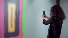 Brunette woman is taking photo of abstract picture in exhibit using smartphone. Female visitor of art gallery is photographing artwork by mobile phone. She is stock video