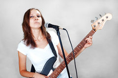 Female vocalist with microphone and bass guitar  on gray Stock Image