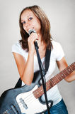 Female vocalist with microphone and bass guitar  on gray Stock Photo