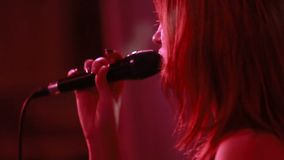Female singer with a microphone on stage stock footage
