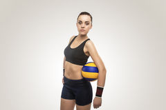 Female Volleyball Athlete in Training Outfit Poses Against Gray Royalty Free Stock Photography