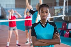 Female volleyball player standing with arms crossed in the court. Portrait of female volleyball player standing with arms crossed in the court Stock Photos