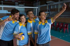 Female volleyball player with team taking selfie. From mobile phone at court Royalty Free Stock Images