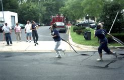 Female volunteer firefighters  carry hise lines stock photos