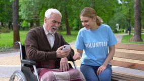 Female volunteer helping disabled old man use smartphone, nursing home charity
