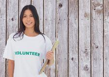 Female volunteer holding a clipboard against wooden background Stock Photo