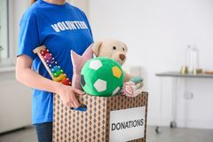 Female volunteer holding donation box with toys. Indoors royalty free stock image