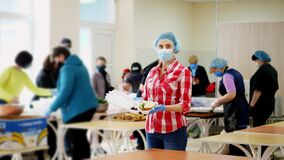 Female volunteer in mask and gloves holds in hands a foam lunchbox with Charity hot meal for poor, homeless people