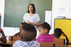 Female volunteer teacher in front of class at an elementary school royalty free stock photo