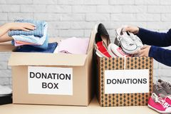 Female volunteers collecting clothes. And shoes into donation boxes indoors Stock Image