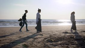 Female volunteers are walking with plastic bags over wild sand beach in daytime, cleaning city territory