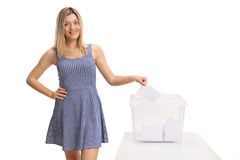 Female voter casting a vote into a ballot box Royalty Free Stock Photos