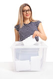 Female voter casting a vote into a ballot box. And looking at the camera isolated on white background Stock Photo