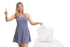 Female voter casting vote into ballot box Royalty Free Stock Image