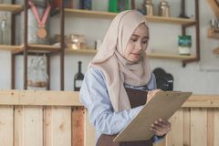 Female waiter in apron writing order. Happy asian male waiter using apron writing order. muslim entrepreneur concept Royalty Free Stock Photos