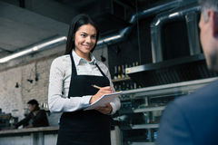 Female waiter in apron writing order Stock Photo