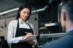 Female waiter in apron writing order. In restaurant Stock Images