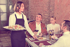 Female waiter bringing order to visitors Stock Photography