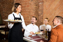 Female waiter carrying order for visitors Royalty Free Stock Images