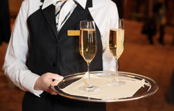 Female waiter with champagne flutes Stock Photo
