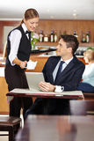 Female waiter serving businessman in coffee shop stock image