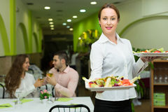 Female waiter serving guests table Stock Image