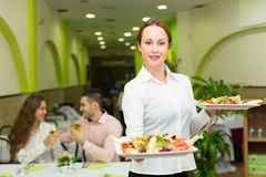 Female waiter serving guests table Stock Photography