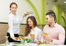Female waiter serving guests table Royalty Free Stock Images