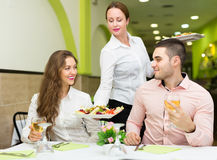 Female waiter serving guests table Royalty Free Stock Photos