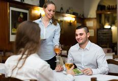 Female waiter serving guests table Royalty Free Stock Photography