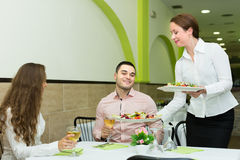 Female waiter serving guests table Royalty Free Stock Photo