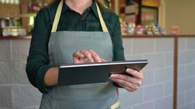 Female waiter takes an order from a customer using a tablet in a small cafe