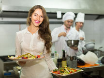 Female waiter taking dish at kitchen Royalty Free Stock Photography