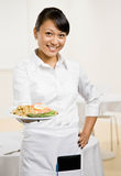Female waiterss offers plate of food Stock Photo