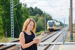 Female waiting train on the platform Stock Photography