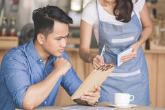Female waitress explain about the menu to her customer. Portrait of female waitress explain about the menu to her cutomer Royalty Free Stock Photography