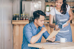 Female waitress explain about the menu to her customer. Portrait of female waitress explain about the menu to her cutomer Royalty Free Stock Photo