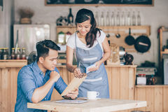 Female waitress explain about the menu to her customer Royalty Free Stock Photos