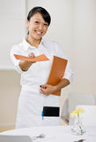 Female waitress offers menu. Happy waitress offering menu in elegant restaurant Stock Photography